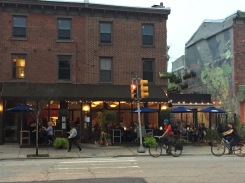 Fare Restaurant with outdoor dining and mural with vertical garden.